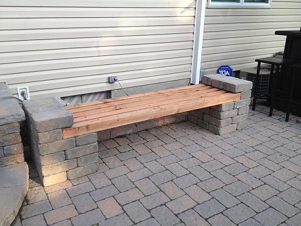 Slim gebruik van een restje straatstenen als bouwmateriaal voor een tuinbank.