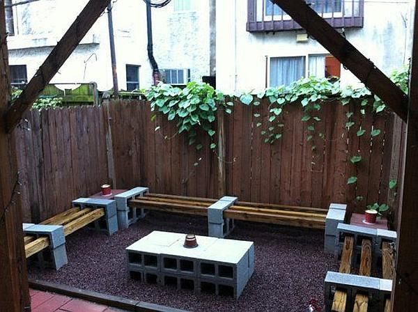 Achtertuintje met tuinmeubelen gemaakt van open betonblokken en sloophout.