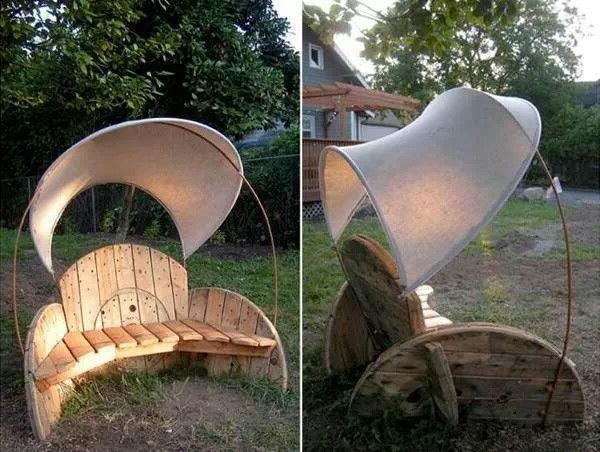 Een gedemonteerde houten haspel als tuinstoel met overkapping voor schaduw.