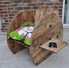 Houten kabelhaspel in gebruik als stoel voor in de tuin.