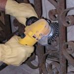 Metalen hekwerk van smeedijzer roestvrij maken met een staalborstel.