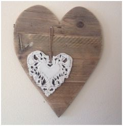 Dit bord van steigerhout heeft een hartvorm.