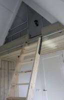 Leuk bed in de punt van een dak, plaatsbesparend bed van steigerplanken en steigerbuis.