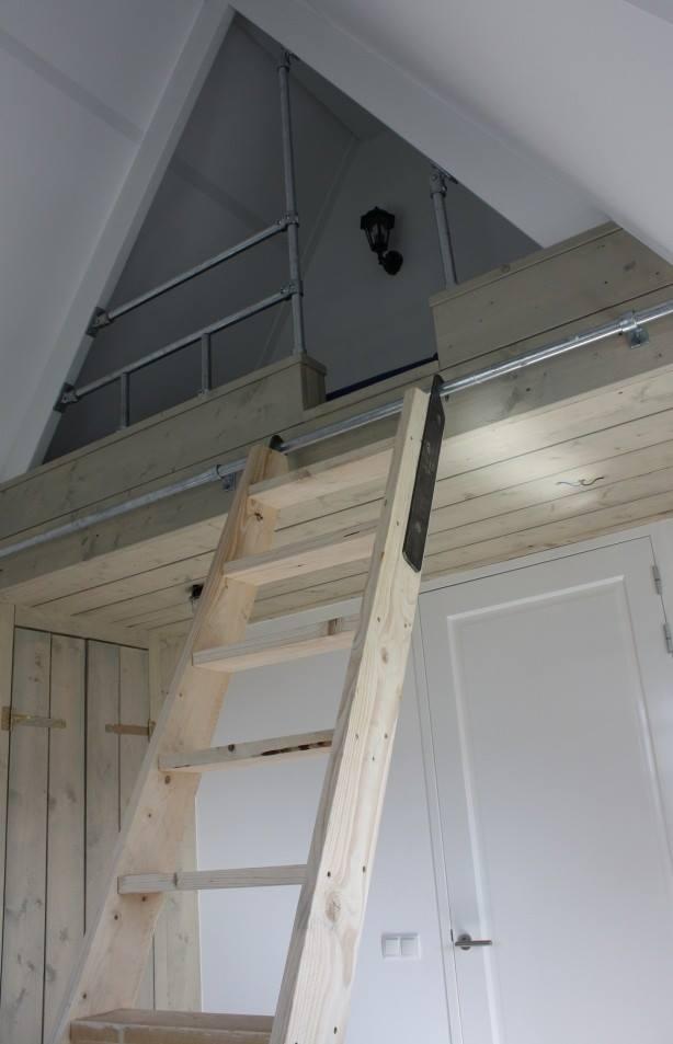 Leuk hoogslaper bed in de punt van een dak, plaatsbesparend bed van steigerplanken en steigerbuis.